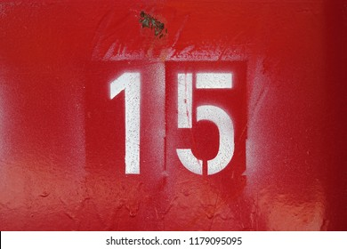 number 15 , white stencil letters on red background