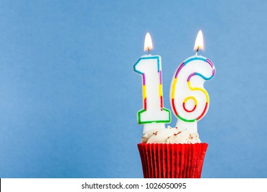 Number 16 birthday candle in a cupcake against a blue background