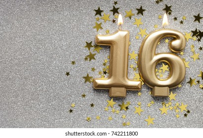Number 16 gold celebration candle on star and glitter background