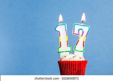 Number 17 birthday candle in a cupcake against a blue background