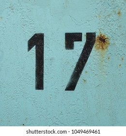 number 17, black stencil numbers on blue background, seventeen