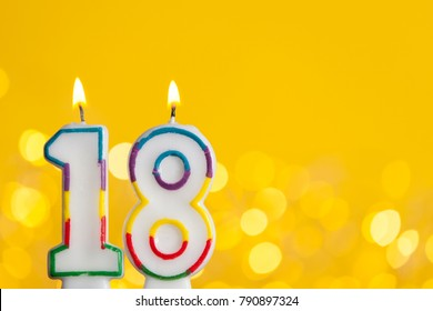 Number 18 birthday celebration candle against a bright lights and yellow background