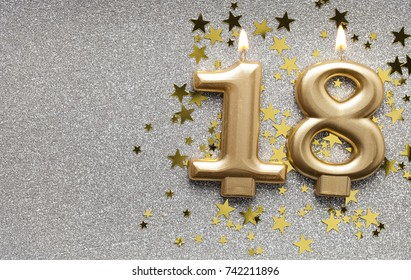 Number 18 gold celebration candle on star and glitter background