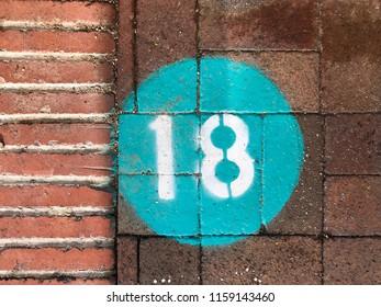 Number 18 spray painted on a sidewalk