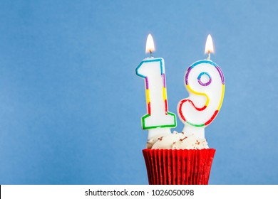 Number 19 Birthday Candle In A Cupcake Against Blue Background