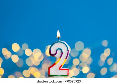 Number 2 birthday celebration candle against a bright lights and blue background