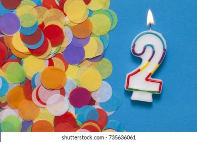 Number 2 celebration candle with party confetti