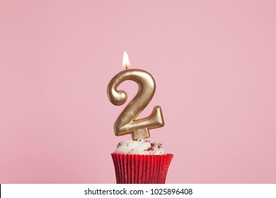 2nd Birthday Party Invitation Card Number 2 Gold Candle In A Cupcake Against Pastel Pink Background
