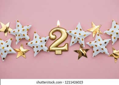 Number 2 gold candle and stars on a pastel pink background