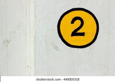 Number 2 sign painted on a white wall in yellow and black color