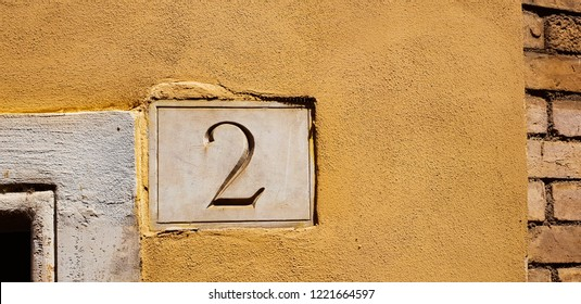 Number 2 (two) isolated on the yellow wall