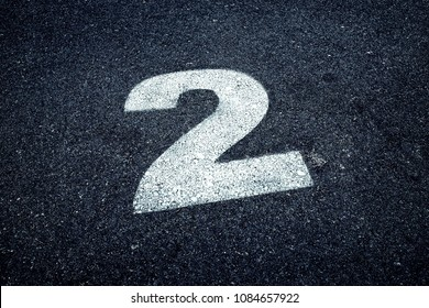 Number 2 (two) painted with white paint on asphalt, copy space