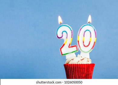 Number 20 Birthday Candle In A Cupcake Against Blue Background