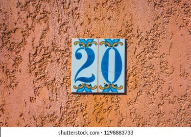number 20 door sign on orange facade