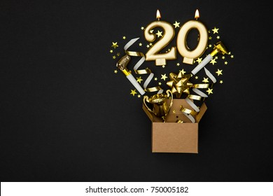 Number 20 gold celebration candle and gift box background