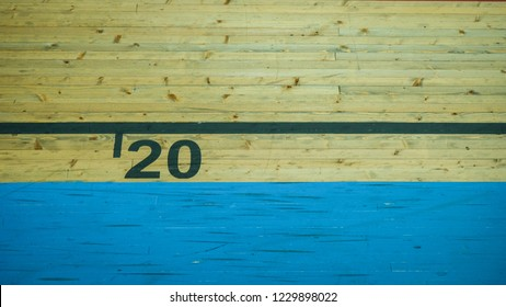 Number 20 (twenty) in black lettering on vintage moody wooden texture with blue stripe beneath it