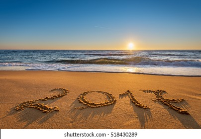 Number 2017 written on seashore sand at sunrise. Concept of upcoming new year and passing of time.