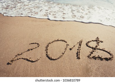Number 2018 written on the sand in the beach