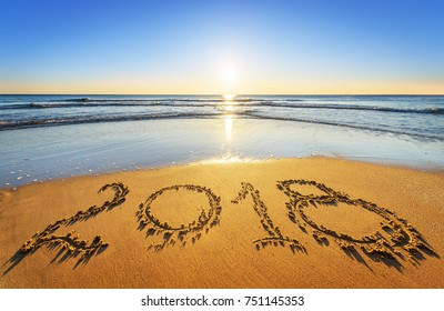 Number 2018 written on seashore sand at sunrise. Concept of upcoming new year and passing of time.