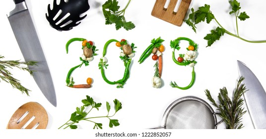 Number 2018 written with vegetables and kitchen utensils as advertising or presentation in food industry, menus, brochures. Isolated on white background. Happy new year. End of the year resolution