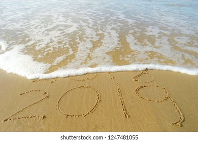 Number 2019 and part of 2018 written on sand beach with part of 2018 erase by wave water. New year concept for leaving 2018 to enter 2019