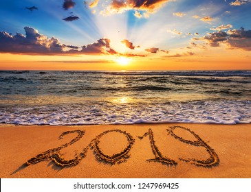 Number 2019 written on seashore sand at sunrise. Concept of upcoming new year and passing of time.