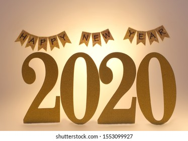 Number 2020 and Blurry Happy New Year Sign in Background on White