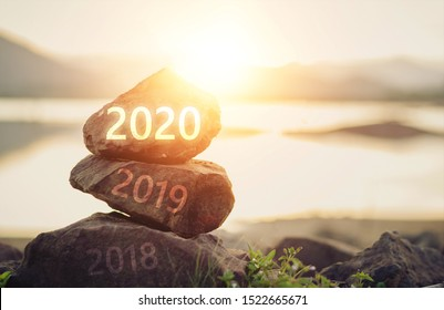 Number 2020  on stone the beach at sunrise. Concept Happy new year.
