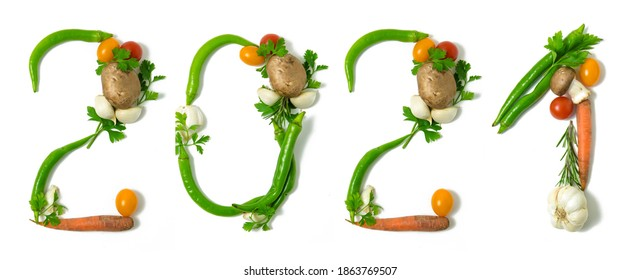 Number 2021 and healthy written with vegetables, concept for healthy food, living, covid 19, coronavirus prevention. Isolated on white background. Happy new year. End of the year resolution