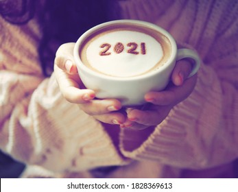 Number 2021 on frothy surface of cappuccino served in white cup holding by female hands with rainbow french nail polish. Holidays food art theme for New Year 2021 celebration. (selective focus)