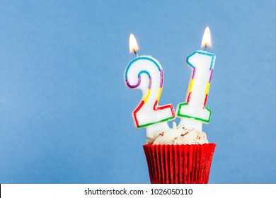 Number 21 Birthday Candle In A Cupcake Against Blue Background