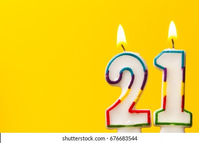 Number 21 Birthday Celebration Candle Against A Bright Yellow Background