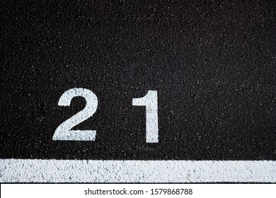 Number 21, legal age, painted on the paved ground of a white-painted parking lot,