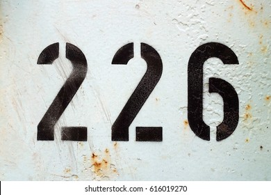 number 226  ,  black stencil letters on white background
