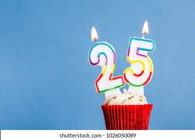 Number 25 birthday candle in a cupcake against a blue background