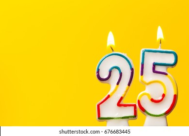 Number 25 birthday celebration candle against a bright yellow background