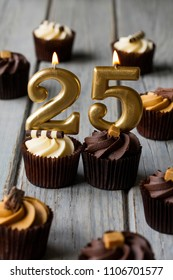 Number 25 celebration birthday cupcakes on a wooden background