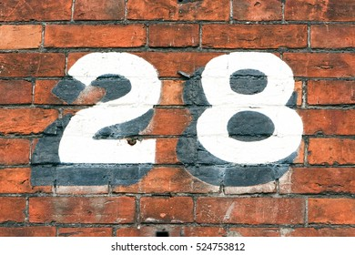 Number 28 painted on brick wall