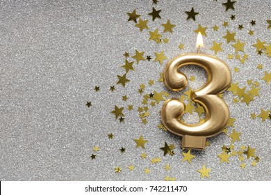 Number 3 gold celebration candle on star and glitter background