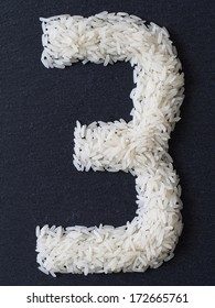 Number 3 made of rice on a black slate