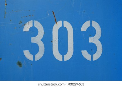 number 303, white stencil letter on blue background