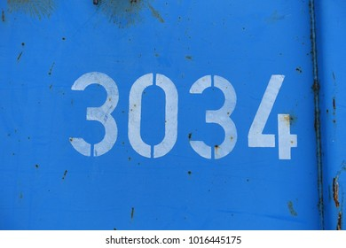 number 3034, white stencil numbers on blue background