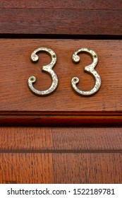 Number 33 on a natural grained wooden front door
