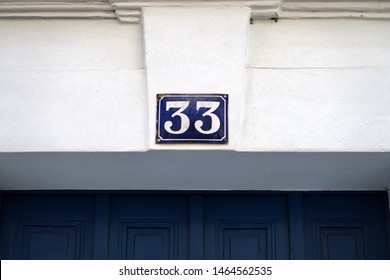 Number 33, street number plate on a facade.