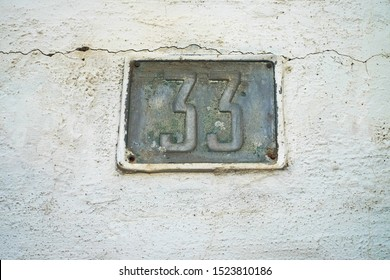 Number 33, thirty-three, old house number plate on a weathered wall background.