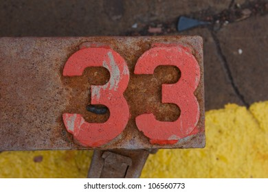 The number 33 (thirty-three) superimposed in red on a rusty piece of equipment at an industrial facility.