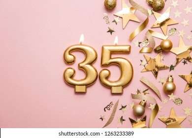Number 35 gold celebration candle on star and glitter background