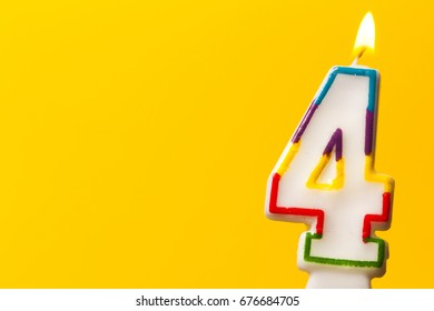 Number 4 birthday celebration candle against a bright yellow background