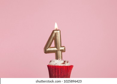 Number 4 Gold Candle In A Cupcake Against Pastel Pink Background