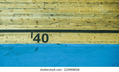 Number 40 in black lettering with wooden textured background and blue stripe beneath it